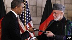 President Barack Obama and Afghan President Hamid Karzai sign a strategic partnership agreement at the presidential palace in Kabul, Afghanistan, May 2, 2012.