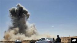 反卡扎菲武装的一个检查站附近在遭到利比亚战机空袭后冒起浓烟