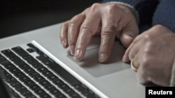 A U.S. cyber warfare expert works on his laptop computer, December 1, 2011.