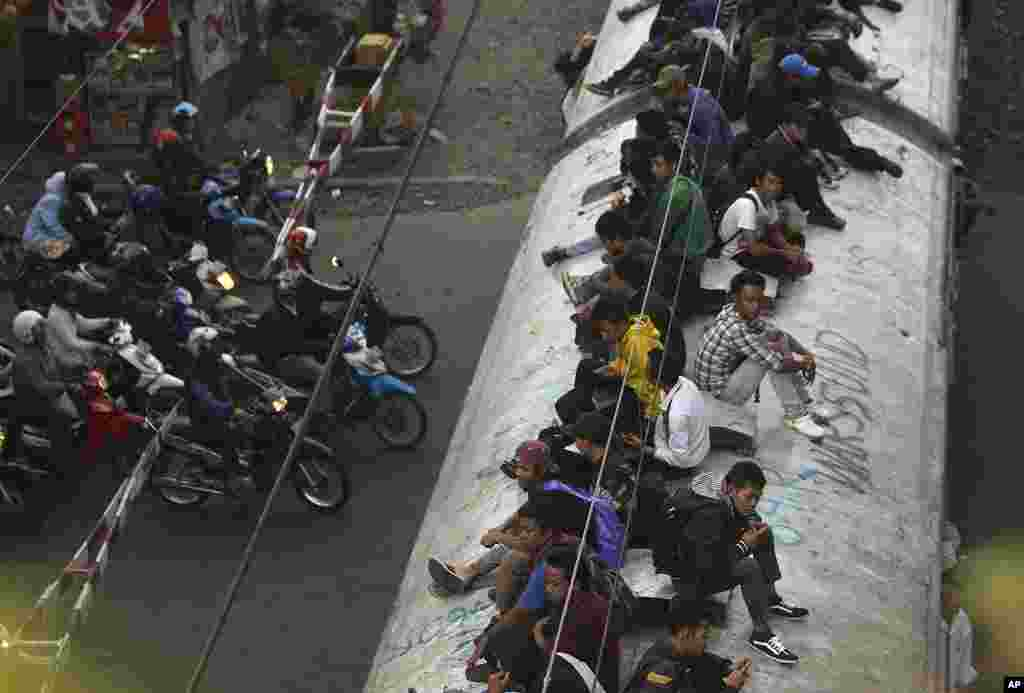 People ride on top of a crowded commuter train in Jakarta, Indonesia, January 17, 2012. (AP)
