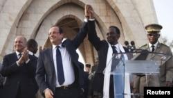 Le président François Hollande de France (2e G) joint les mains avec le président intérimaire Dioncounda Traoré du Mali à la place de l'Indépendance à Bamako, au Mali 2 février, 2013.