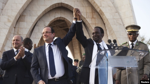 France's President Francois Hollande (2nd L) joins hands with Mali's interim president Dioncounda Traore at Independence Plaza in Bamako, Mali February 2, 2013.
