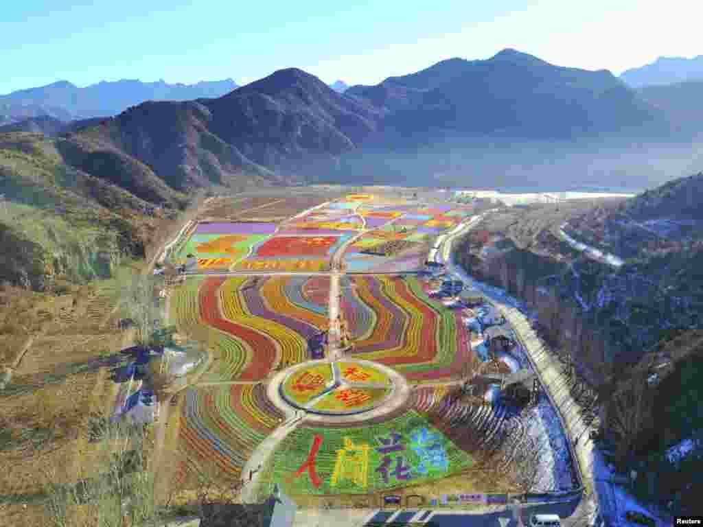 """کلمههای «خوشبختی"""" و «موفقیت"""" با آسیابهای بادی در یک نقطه گردشگری نوشته شده است.  پکن، چین."""