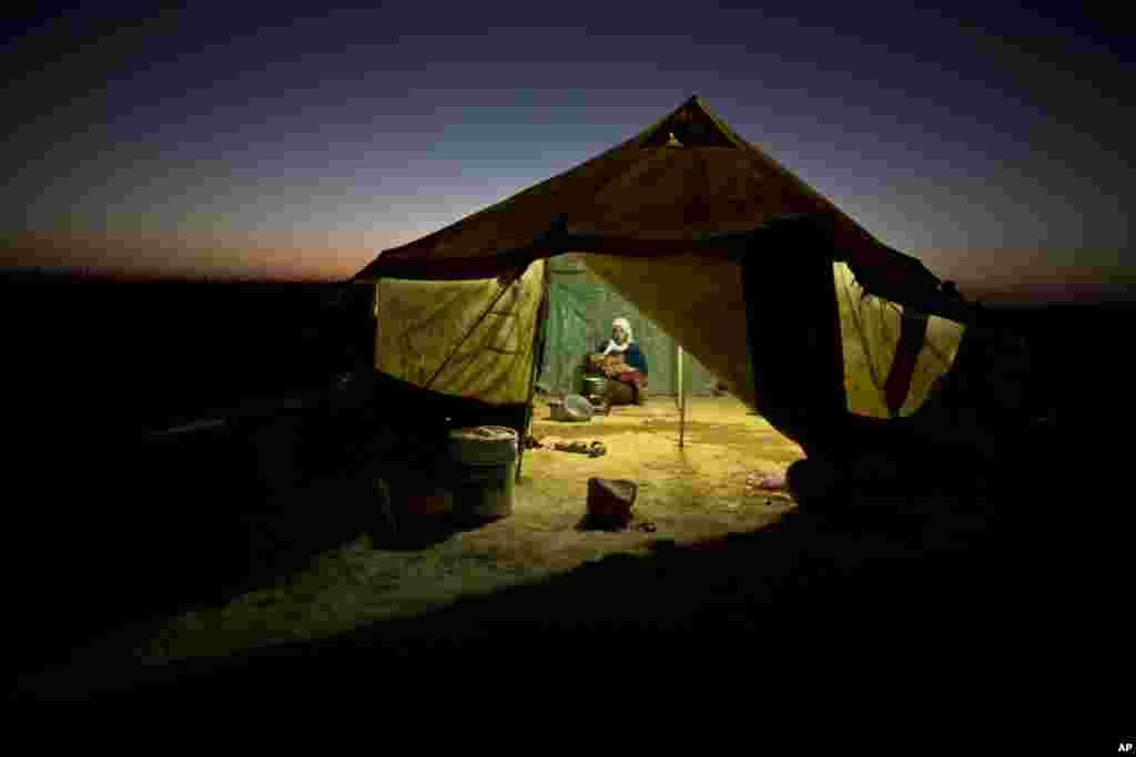 Seorang pengungsi Suriah mengasuh anaknya sambil memasak di dalam tendanya di sebuah tempat penampungan tidak resmi dekat perbatasan Suriah di pinggiran kota Mafraq, Yordania.