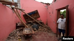 Humberto Cruz stands inside his house destroyed by the earthquake that struck the southern coast of Mexico late on Thursday, in Ixtaltepec, Mexico, Sept. 10, 2017.