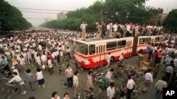 资料照:大批人群在北京一处交叉路口试图用公共汽车和路障拦阻军队向天安门广场推进。(1989年6月3日)