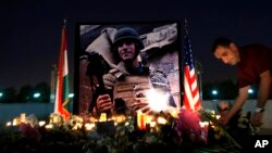 Seorang pria meletakkan bunga di sebuah tempat peringatan bagi jurnalis AS yang tewas, James Foley, di Irbil, Irak (24/8).