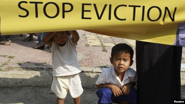 A Cambodian girl holds a banner next to a boy as former residents of the Dey Krahorm community gather in front of the site where they used to live before being evicted by government forces in Phnom Penh January 24, 2012.