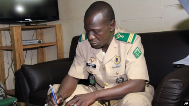 Mali's military junta leader, Captain Amadou Sanogo signs documents as the junta and the West African bloc ECOWAS announced a deal that includes the lifting of sanctions and an amnesty for those involved in last month's coup at the Kati military camp, nea