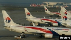 Ground crew work among Malaysia Airlines planes on the runway at Kuala Lumpur International Airport (KLIA) in Sepang, July 25, 2014.