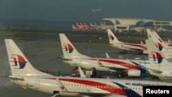 FILE - Ground crew work among Malaysia Airlines planes on the runway at Kuala Lumpur International Airport in Sepang.