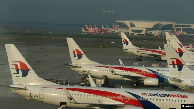FILE - Ground crew work among Malaysia Airlines planes on the runway at Kuala Lumpur International Airport (KLIA).