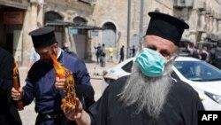 Священник Греческой православной церкви с благодатным огнем, Иерусалим, 18 апреля 2020 года