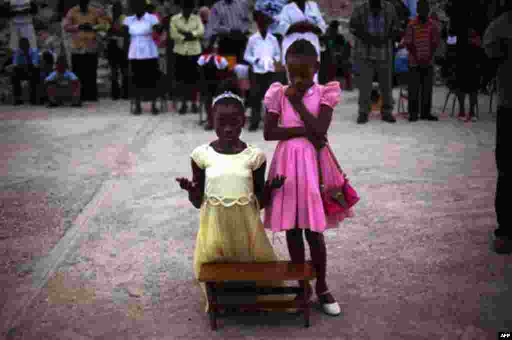Smeralda, 12, kneeling, and her sister Serena, 11, pray during mass next to the rubble of the Notre Dame Cathedral in Port-au-Prince, Haiti, Sunday Nov. 14, 2010. (AP Photo/Emilio Morenatti)