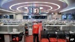 Yip Wing-keung, manajer perdagangan di perusahan sekuritas Christfund Securities, mengenakan jaket merah berjalan di Bursa Saham Hong Kong, 19 Oktober 2017.