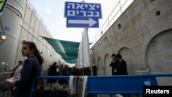 FILE - A sign pointing to the men's exit is seen at Rachel's Tomb in the West Bank town of Bethlehem, November 8, 2011.