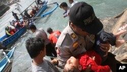 常有從印尼往澳大利亞尋求避難的船隻遇難。7月24日澳大利亞一名警察手抱一昏迷的幼童。