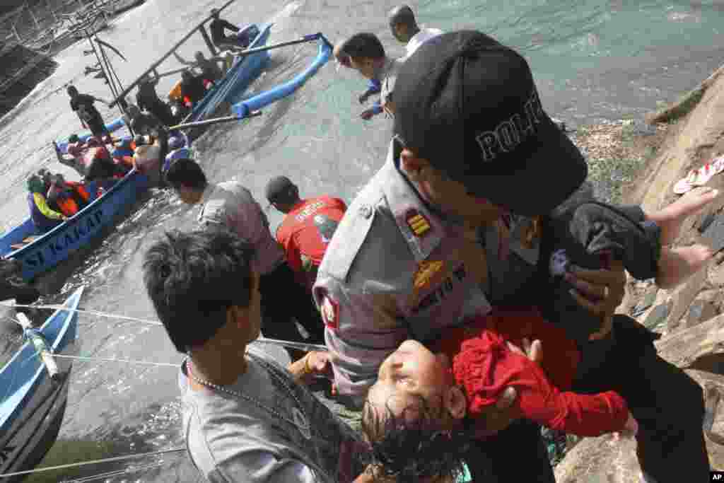 A police officer carries a child who appears to be unconscious after a boat carrying asylum seekers sank off  West Java, Indonesia, July 24, 2013.