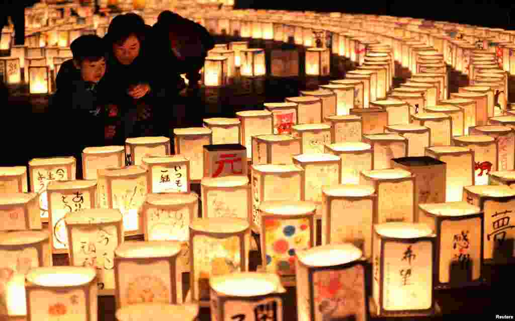 A family looks at paper lanterns during a memorial event to mourn victims of the March 11, 2011 earthquake and tsunami disaster, in Natori, Miyagi prefecture, Japan, in this photo taken by Kyodo March 11, 2017.