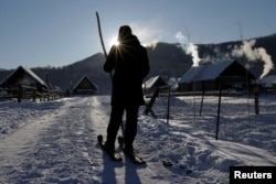 Local villager Sulita, wearing traditional horsehide skis, makes his way home in Khom village of Altay, Xinjiang Uighur Autonomous Region, China, Jan. 27, 2018.