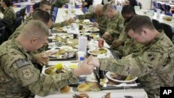 U.S. soldiers pray before eating a Thanksgiving meal at a dining hall at the U.S.-led coalition base in Kabul, Afghanistan, Nov. 22, 2012.