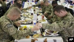 U.S. soldiers pray before eating a Thanksgiving meal at a coalition base dining hall, Kabul, Afghanistan, Nov. 22, 2012.