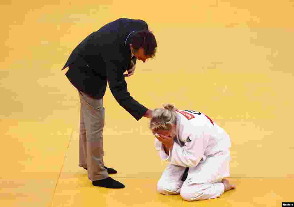 El árbitro pregunta sobre la salud dela alemana Kerstin Thiele durante su pelea con la china Chen Fei en la semi final de judo de mujeres de menos de 70 kilos.