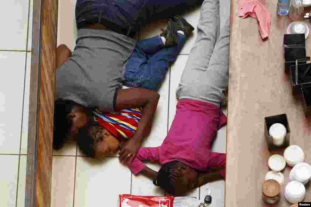 2013年9月21日,在内罗毕遭到袭击的韦斯特盖特购物中心,一名母亲和她的孩子躲避枪手的追击。
