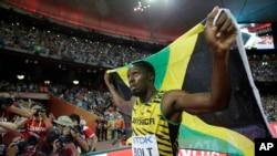 Pelari Jamaika Usain Bolt merayakan kemenangan meraih medali emasi 100 meter pria di Kejuaraan Atletik Dunia di Beijing (23/8). (AP/Lee Jin-man)