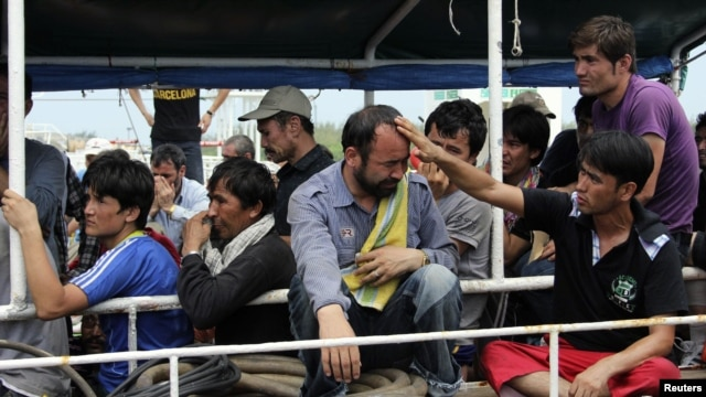 Asylum seekers from Afghanistan, Iraq and Iran cry as Indonesian officers force them to leave the Australian vessel Hermia docked at Indah Kiat port in Merak, Indonesia's Banten province, April 9, 2012.