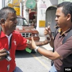 Seorang polisi berpakaian preman mencoba memborgol seorang aktivits (kiri) pada aksi protes Hari Buruh, 1 Mei lalu di Kuala Lumpur.