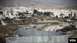 """Israel menyetuji pembangunan permukiman baru di kawasan permukiman """"Pisgat Zeev"""" di Yerusalem Timur (atas) yang tampak dilindungi oleh pagar beton pemisah."""