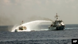 Kapal patroli Vietnam (kiri) terlibat tembak menembak meriam air dengan kapal China di perairan sengketa Laut China selatan, Senin 12/5 (foto: dok).