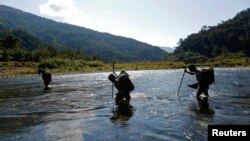 FILE - Naga men are seen walking through a creek in the Naga Self-administered Zone in northwest Myanmar.