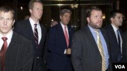 ລັດຖະມົນຕີຕ່າງປະເທດ ສຫລ ທ່ານ John Kerry (ກາງ) ກໍາລັງເດີນທາງກັບໄປໂຮງແຮມ ຫລັງຈາກປະຊຸມກັບຄູ່ຕໍາແໜ່ງ ຝ່າຍອີຣ່ານ ທ່ານ Mohammad Jarad Zarif