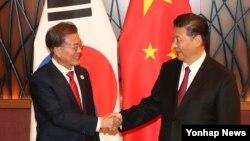 Presiden Korea Selatan Moon Jae-in (kiri) berjabat tangan dengan Presiden China Xi Jinping saat bertemu di KTT APEC, Vietnam, 11 November 2017 (Foto: dok).