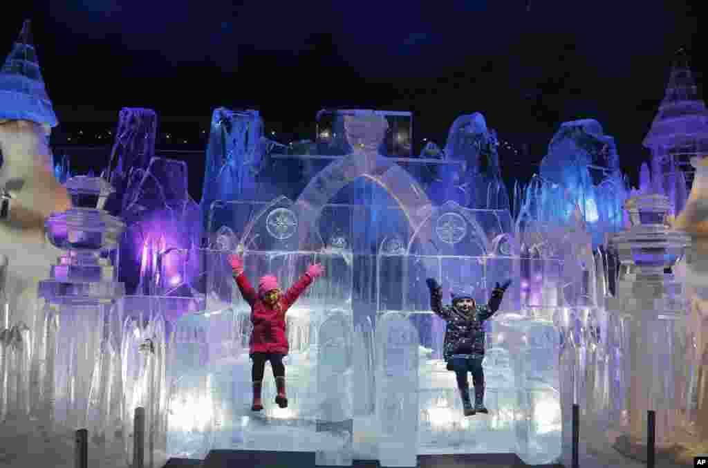កុមារី Scarlett អាយុ ០៤ឆ្នាំ និង Zoe អាយុ ០៣ឆ្នាំ លេងនៅក្នុងរូបចម្លាក់ទឹកកករាងជាប្រាសាទនៅអំឡុងពេលសម្ពោធឧទ្យាន Hyde Park Winter Wonderland's Magical Ice Kingdom ក្នុងក្រុងឡុងដ៍។