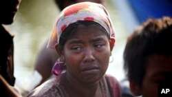 FILE - A rescued migrant weeps upon arrival in Simpang Tiga, Aceh province, Indonesia, Wednesday, May 20, 2015. Authorities in Aceh are preparing to tow a boat with more than 40 Tamil men, women and children out to sea Friday after rescuing it last weekend.
