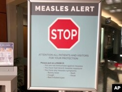 Signs posted at a clinic in Vancouver, Washington warns patients and visitors of a measles outbreak. A measles outbreak near Portland, Ore., has revived a bitter debate over personal belief exemptions to childhood vaccinations, 2019. (File Photo)