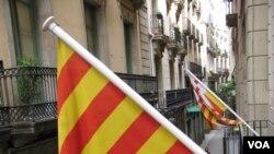 Warga Barcelona pendukung otonomi Catalonia ikut mengibarkan bendera Catalonia.