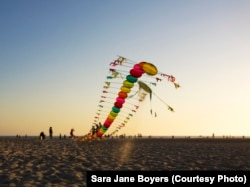 Tyrus Wong's centipede kite begins to rise into the sky above Santa Monica Beach.