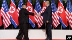 Le président américain Donald Trump tend la main au dirigeant nord-coréen Kim Jong Un à la station balnéaire de Capella sur l'île de Sentosa le mardi 12 juin 2018 à Singapour.