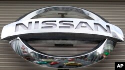 FILE - Vehicles are reflected on the logo of the Nissan Motors Co. at a showroom in Tokyo's Ginza shopping district, Japan.
