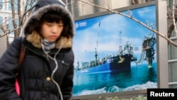 Woman walks past a poster showing an offshore work platform from of China National Offshore Oil Corp. (CNOOC), outside its Beijing headquarters, Dec. 2012 file photo.