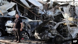FILE - A man inspects site of car bomb explosion in Baghdad's eastern Mashtal neighborhood, Iraq, Nov. 17, 2014.