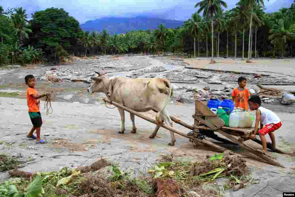 Filipinler'de meydana gelen sel baskınlarının ardından, küçük çocuklar köylerine temiz içme suyu taşıyorlar.
