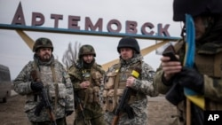 FILE - Ukrainian servicemen stand at the sign reading Artemivsk, eastern Ukraine, March 3, 2015. Some European Union member states want to give the fragile cease-fire with Russia more time.
