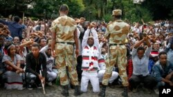 FILE - Ethiopian soldiers try to stop protesters in Bishoftu, in the Oromia region of Ethiopia.