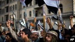 Shi'ite Houthi rebels hold up their weapons at a rally against Saudi-led airstrikes against them, in Sana'a, Yemen, April 10, 2015.