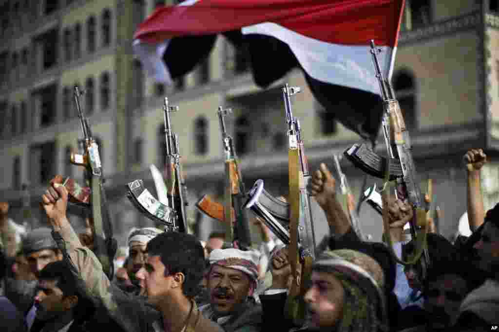 Shiite rebels, known as Houthis, hold up their weapons as they attend a protest against Saudi-led airstrikes in Sanaa, Yemen. Pakistani lawmakers on Friday unanimously voted to stay out of the Saudi-led air coalition targeting Shiite rebels in Yemen in a blow to the alliance.